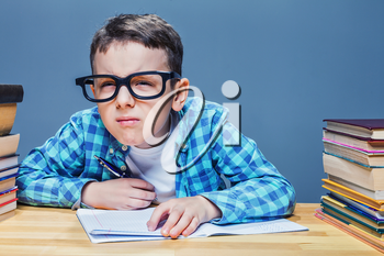 Pupil in glasses squints, bad vision concept. Young schoolboy sitting at the desk against many books