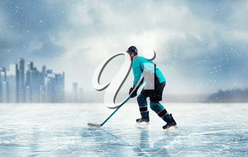 Professional ice hockey player in action on frozen lake, cityscape on background. Ice-skating outdoors. Winter season sport
