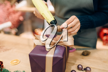 Female seller decorates gift box with fir cone, handmade wrapping and decoration process. Woman wraps present on the table, decor procedure