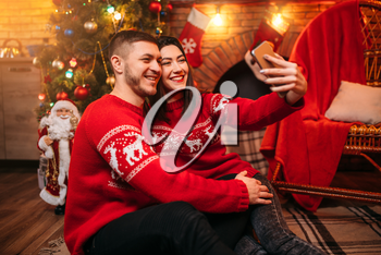 Love couple makes selfie on phone camera, romantic xmas celebration. Christmas holidays, man and woman happy together, festive decoration on background