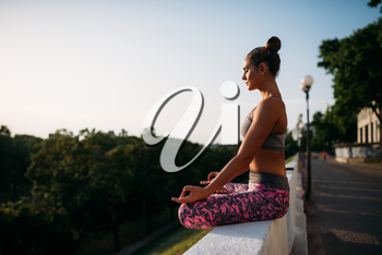 Young woman sitting in yoga pose, city on background. Yogi training outdoors, relaxation exercise