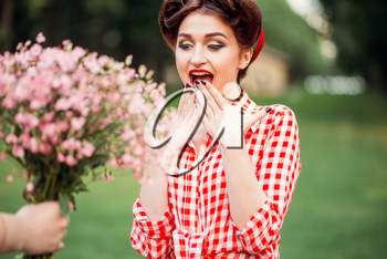 Glamour pinup girl takes gift a bouquet of flowers, retro american fashion. Attractive woman in pin up style