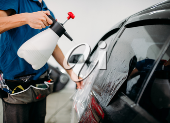 Male hand with spray, car window tint installation process, installing procedure, tinting film