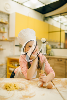 Little girl cook in cap and apron holds whisk for mixing, cookies preparation on the kitchen. Kids cooking pastry, children chefs preparing cake