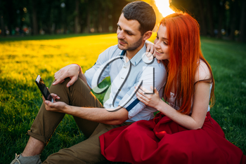Love couple happy together, romantic date in summer park on sunset. Attractive woman and young man leisure on a grass