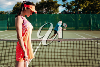 Couple playing tennis on outdoor court. Summer season active sport game