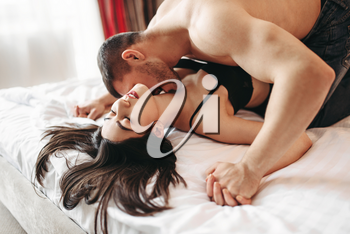 Sexy couple lying and kissing on big white bed. Love games in bedroom, hot sex lovers