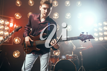 Guitarist plays on bas guitar, rock band, stage with lights on background. Live music concert