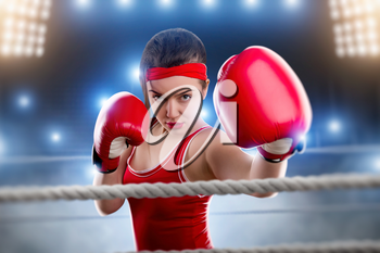 Female boxer in red boxing gloves and sportswear on the ring. Fighting sport concept