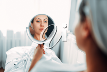 Female patient looks at her face through the mirror, cosmetology clinic. Result of the rejuvenation procedure. Facial skincare in spa salon, beauty medicine