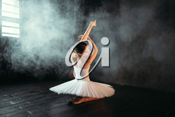 Female classical ballet performer in white dress sitting on the floor, back view. Ballerina training in class with window