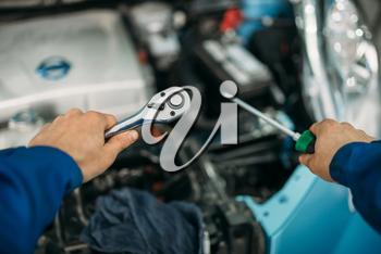 Male technician hands with screwdriver and wrench, car with opened hood on background. Auto-service, vehicle maintenance