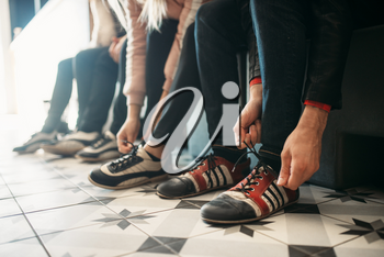 Bowling alley players ties shoelaces on house shoes. Bowlers sitting on the bench and prepares to competition in club, active sport. Bowl sport