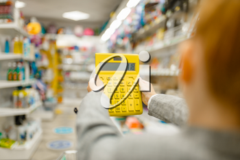 Little schoolgirl holds yellow calculator, shopping in stationery store. Female child buying office supplies in shop, schoolchild in supermarket