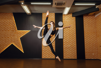 Female contemporary dance performer, jump in motion, training in studio. Dancer on workout in class, modern ballet, elegance dancing, stretching exercise
