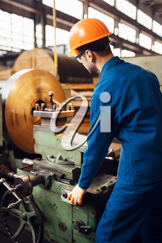 Turner in uniform and helmet works on lathe, factory. Industrial production, metalwork engineering, power machines manufacturing