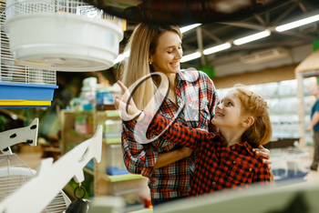 Mother with daughter choosing cage for bird at the showcase in pet store. Woman and little child buying equipment in petshop, accessories for domestic animals