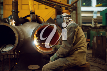 Welder in mask works with big metal pipe on factory, welding skill. Metalworking industry, industrial manufacturing of steel products