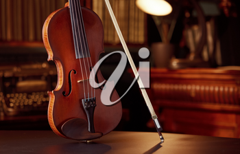 Violin in retro style and bow, closeup view, nobody. Classical string musical instrument, music art, old viola, dark background
