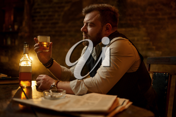 Businessman smokes cigarette and drinks alcohol beverage, vintage office interior on background. Tobacco smoking culture, specific flavor. Male smoker