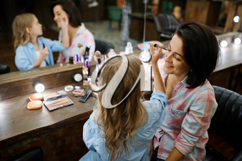 Adorable daughter applies mascara for eyelashes to her mother in makeup salon. Mom and little girl play stylists together, happy childhood, glamour family
