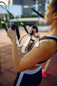 Woman doing exercise with ropes on sports ground outdoors, top view. Slim female person in sportswear, outside fitness training, fit workout