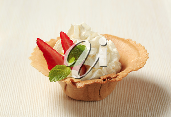 Whipped cream with strawberry in a wafer cup
