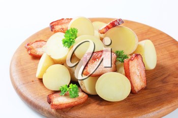 New potatoes and bacon on a cutting board