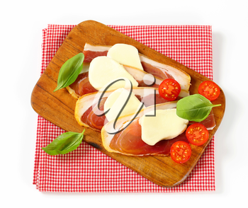 Sliced prosciutto crudo and mozzarella with fresh basil and tomatoes