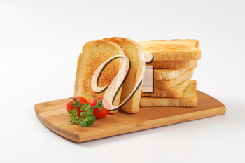 toasted white bread slices on wooden cutting board