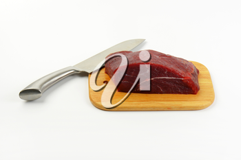 raw beef meat on wooden cutting board and chef's knife