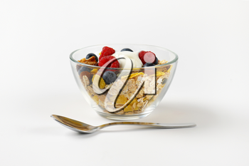 bowl of mixed breakfast cereals with fresh raspberries and blueberries and yogurt