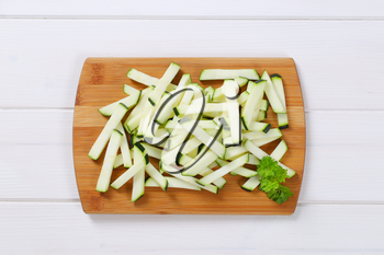 pile of zucchini strips on wooden cutting board