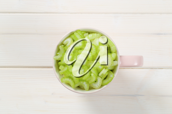 cup of chopped celery stems on white wooden background