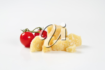 pieces of fresh parmesan cheese and cherry tomatoes on white background