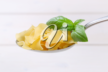 spoon of quadretti - square shaped pasta on white wooden background