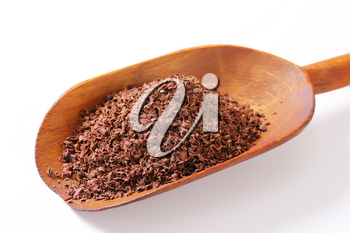 Grated chocolate on wooden scoop