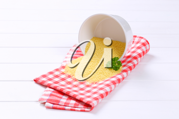 bowl of raw couscous spilt out on checkered place mat