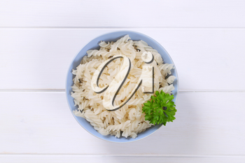 bowl of cooked rice pasta fusilli on white wooden background