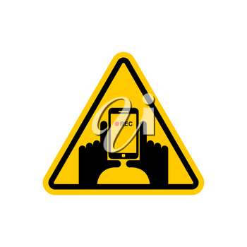 Attention Vertical video. Hand and smartphone to record. Road sign on yellow triangle. symbol Caution