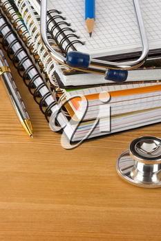 medical stethoscope with notebook at wood table background