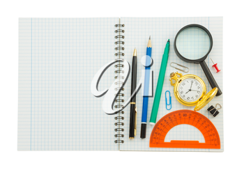 school supplies on checked notebook isolated at white background