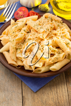 pasta Penne in plate on wooden background