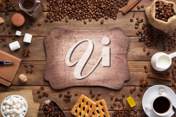 cup of coffee and beans on wooden background table, top view
