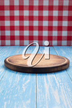pizza cutting board and napkin tablecloth at rustic wooden table, in front plank background
