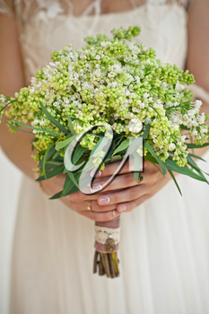 Wedding bouquet in a hand of the bride.