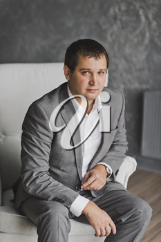 Portrait of business man in suit on the background of the gray wall.
