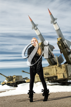 brutal girl standing on a background of military ballistic missiles