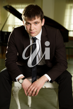 a young man standing near piano in suit