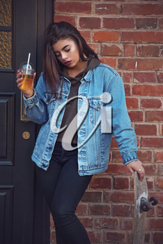 girl with a glass of juice outdoors against a brick house. Skate in the hands